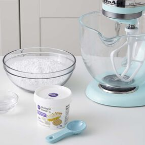 An image of the items needed to make Royal Icing.  A stand mixer, measuring spoon, meringue, and confectioners' sugar