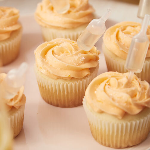 Mimosa Cupcakes with orange frosting and champagne bottle shot top