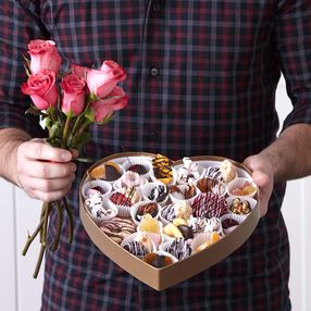 Man holding pink roses and heart shaped box full of Valentine's Day candy