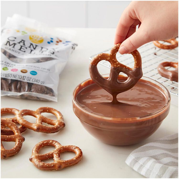 Dipping Pretzels into bowl of melted light Cocoa Candy Melts Candy