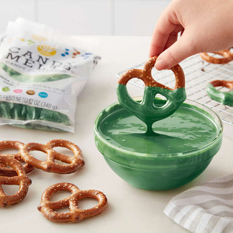 Dipping Pretzels into bowl of melted dark green Candy Melts Candy