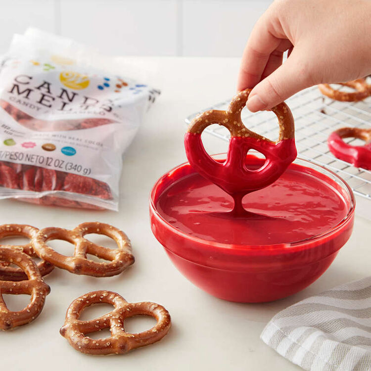 Pretzel being dipped in red Candy Melts