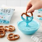 Dipping Pretzels into bowl of melted blue Candy Melts Candy