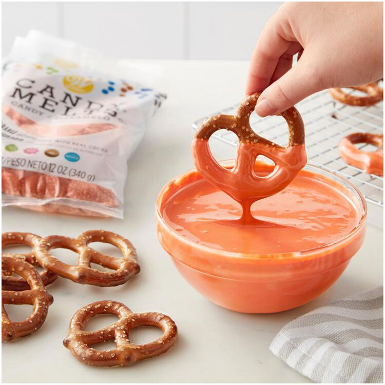 Dipping Pretzels into bowl of melted orange Candy Melts Candy