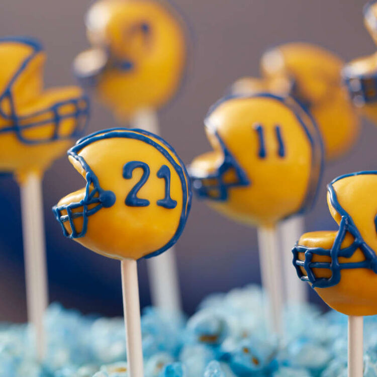 Cake pop helmets decorated in yellow Candy Melts with Royal Blue piping
