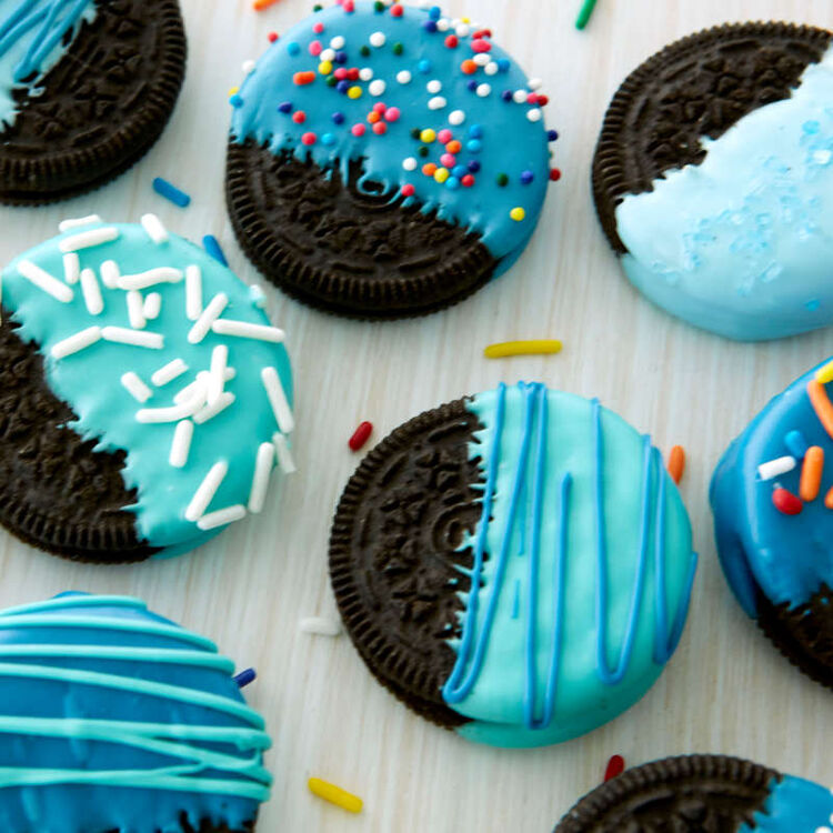 Chocolate sandwich cookies dipped in blue Candy Melts and sprinkles