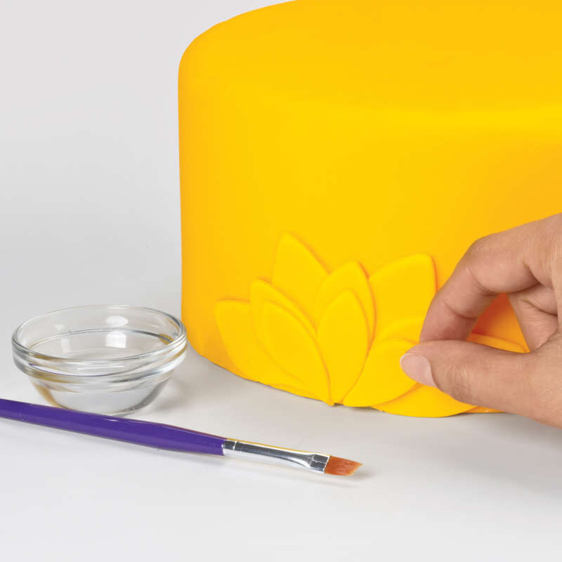 Decorating a Yellow Fondant Cake with Leaves image number 5