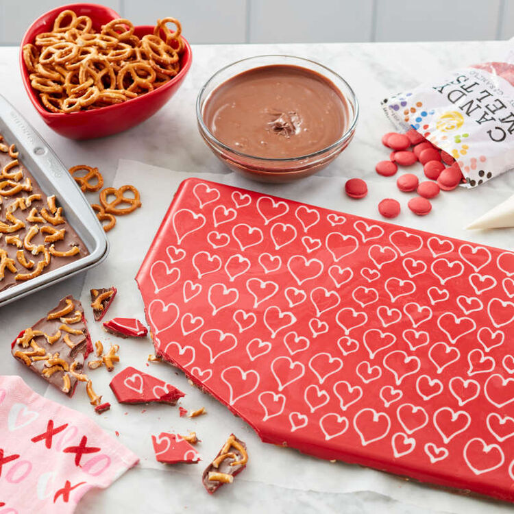 Red with white hearts atop chocolate and pretzel candy bark