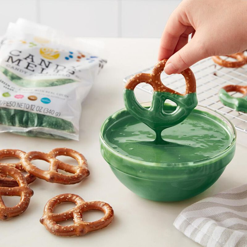 Dipping Pretzels into bowl of melted dark green Candy Melts Candy image number 3