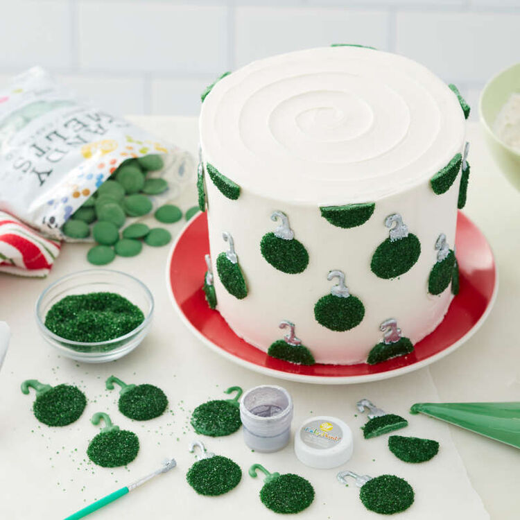Green Candy Melt wafers covered in green sparkling sugar and attached to a cake to look like ornaments