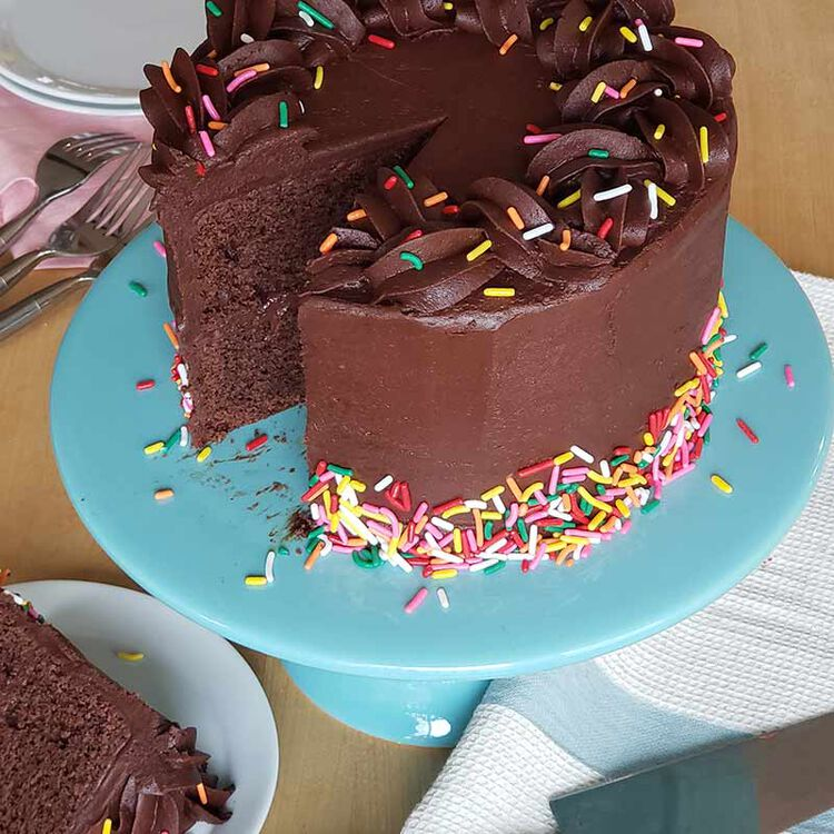 slicing chocolate cake with chocolate buttercream frosting and sprinkles