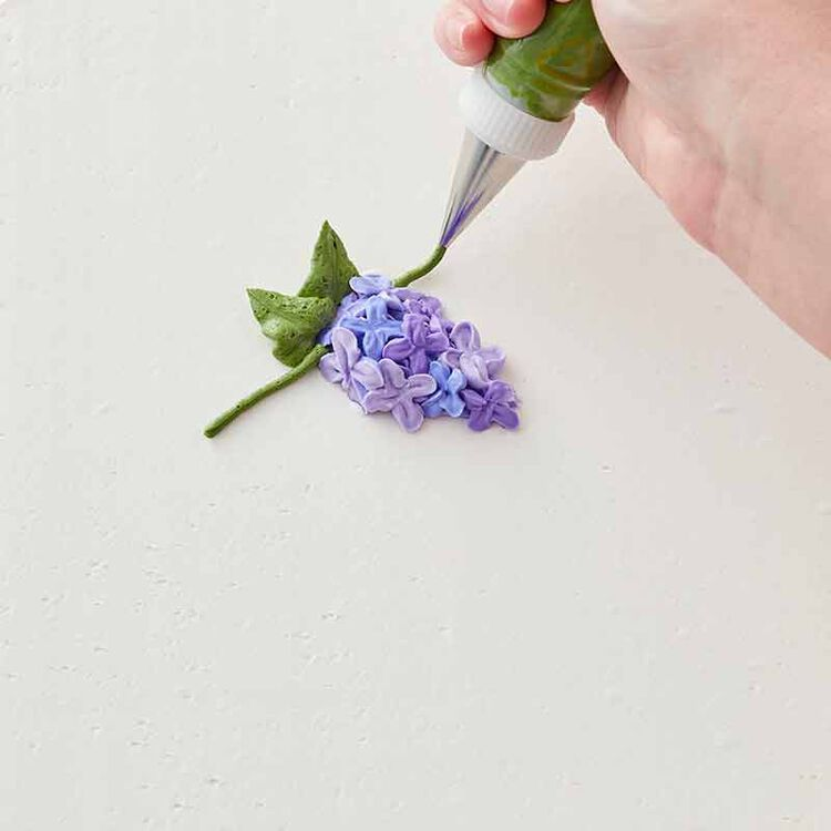 step 5 of piping a buttercream lilac flower