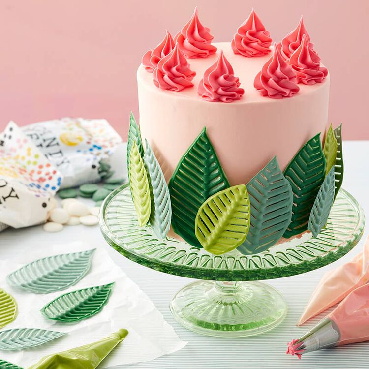 Tropical cake with green candy leaves and topped with pink swirls