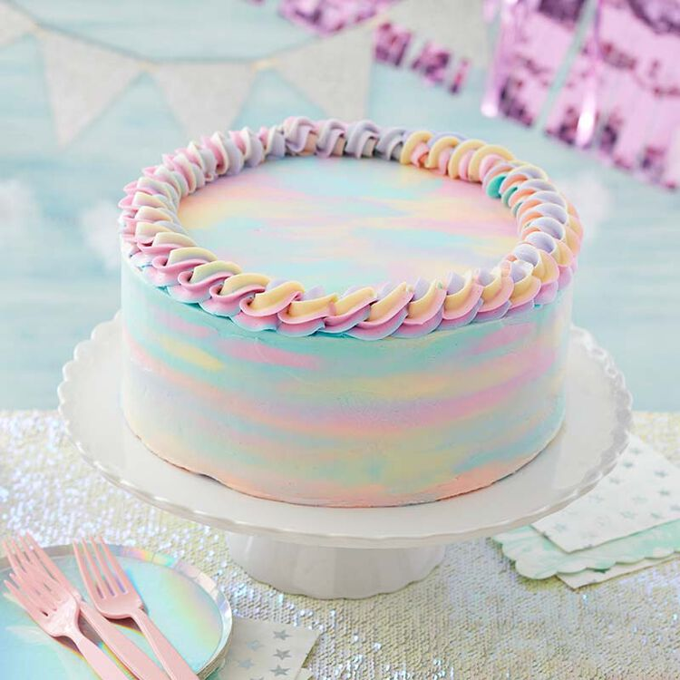 Cake decorated with pastel colored buttercream, spread to look like watercolors