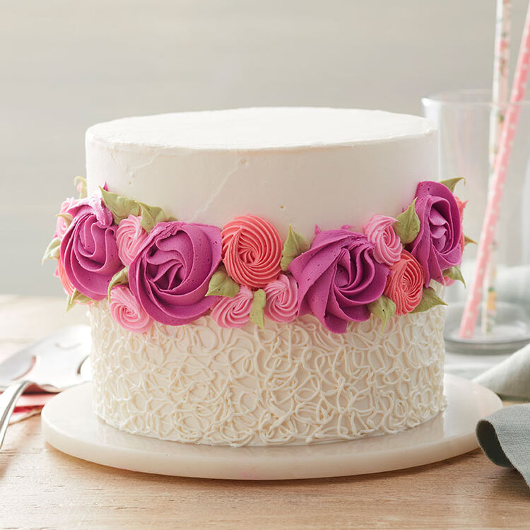 Round cake iced smooth on top with a ring of rosettes around the center and a sotas pattern piped on the bottom in white.