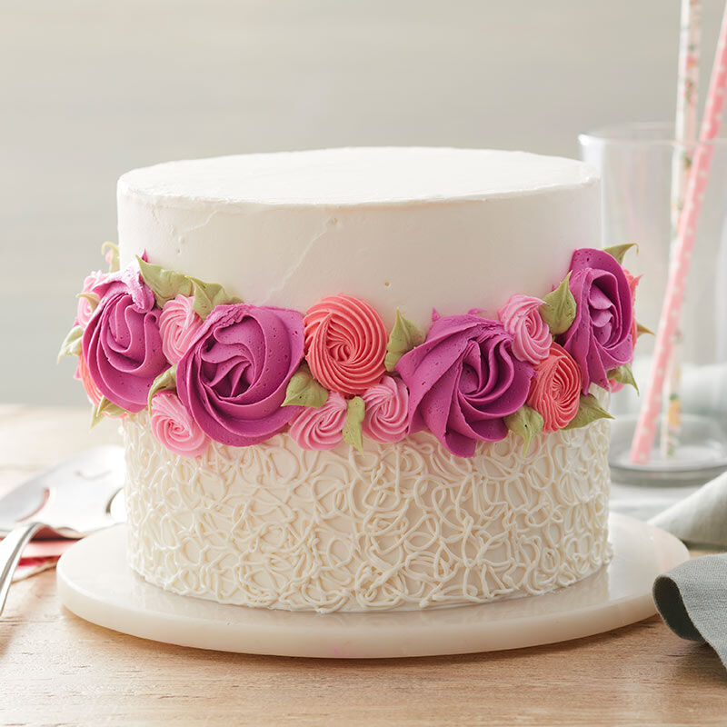 Round cake iced smooth on top with a ring of rosettes around the center and a sotas pattern piped on the bottom in white.  image number 0