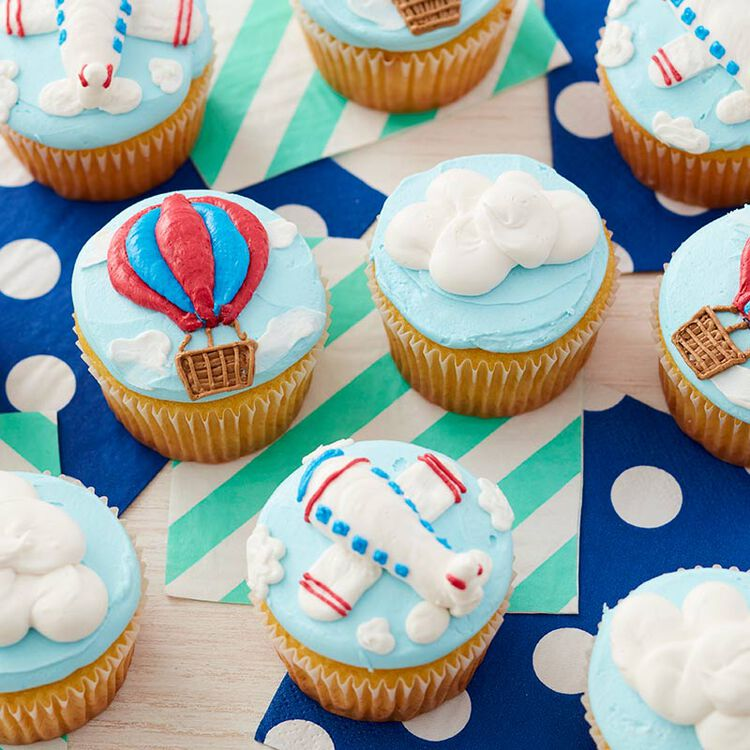 Cupcakes decorated with hot air balloons, airplanes, and clouds