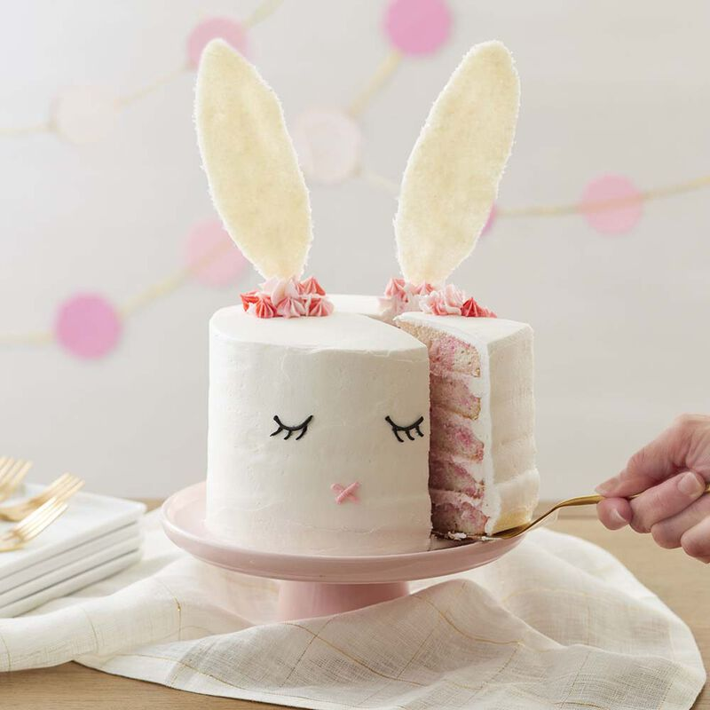 White five layer cake with white buttercream and an easter bunny face with candy ears image number 1