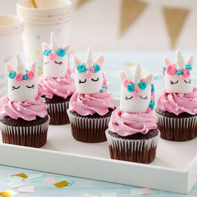 Magical Marshmallow Unicorn Cupcakes- Marshmallows topped with pink buttercream and a unicorn-decorated marshmallow with closed eyes, a pink and blue flower crown, and horns and ears, atop a chocolate cupcake