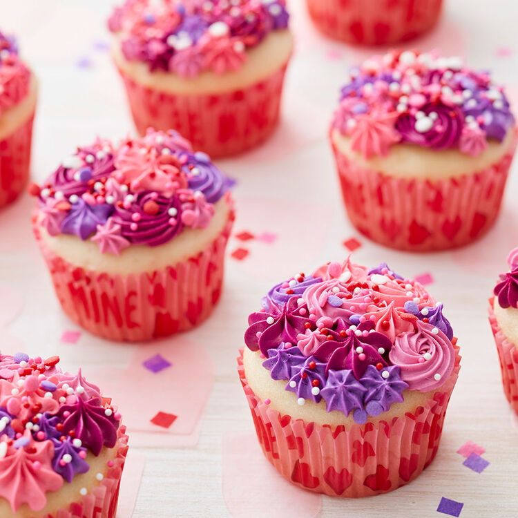 Vanilla cupcakes decorated with shades of pink and purple buttercream piped into rosettes and stars and topped with red, pink, and white sprinkles.