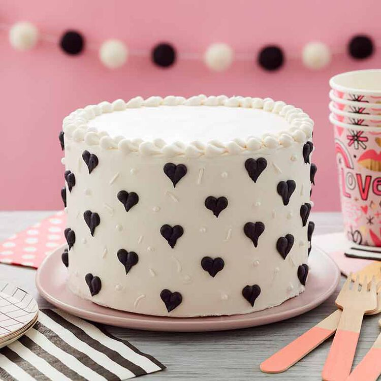 white cake piped with black hearts
