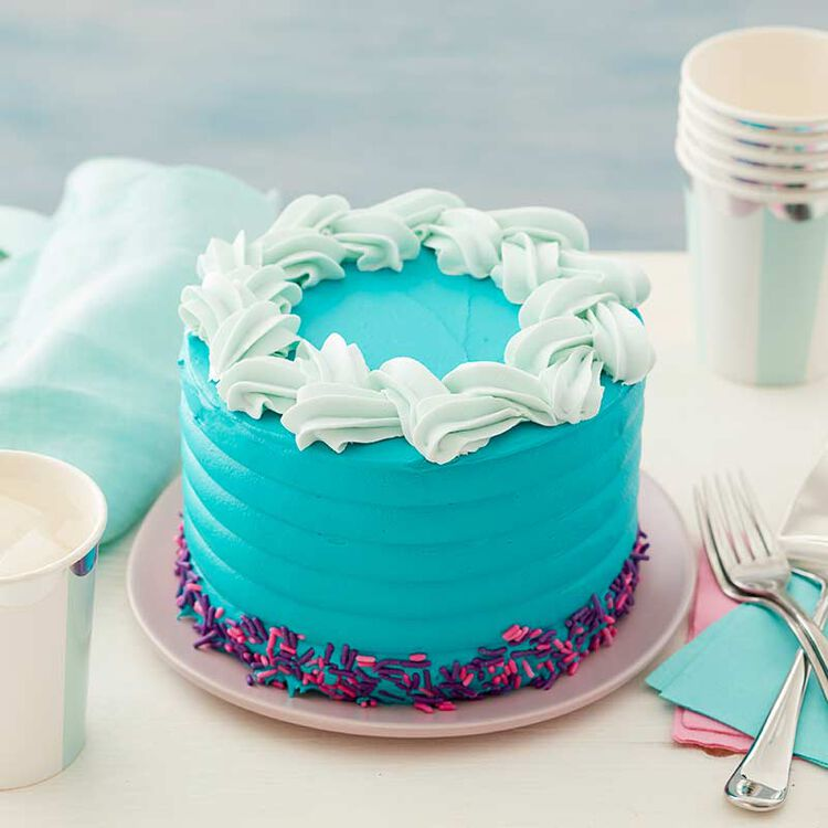 table setting with a turquoise cake displayed and decorated with pink and purple sprinkles and a white braided border.