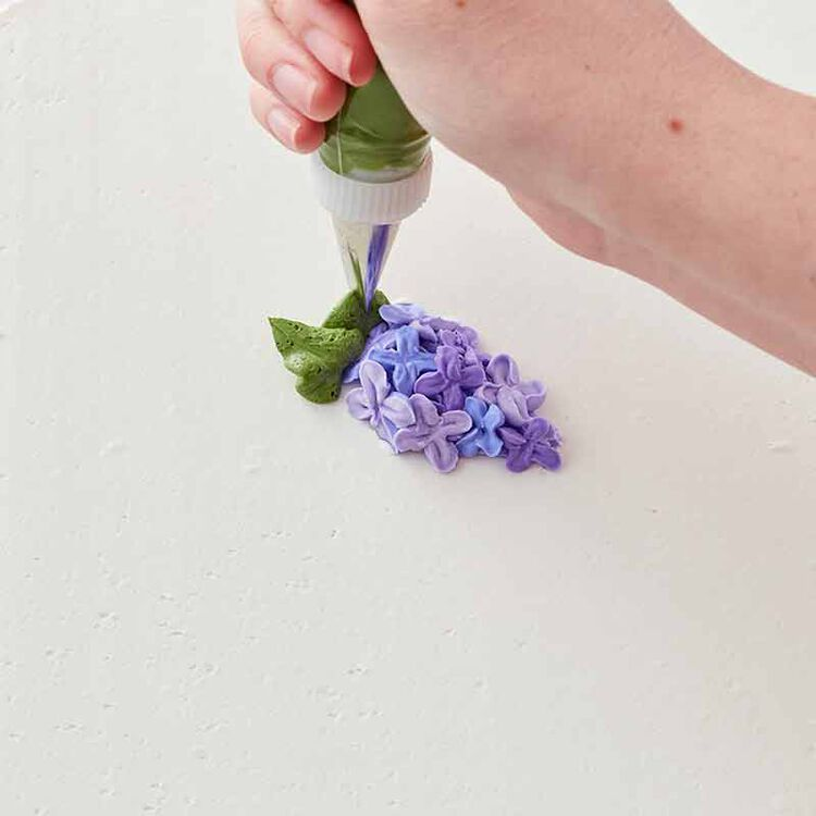 step 4 of piping a buttercream lilac flower
