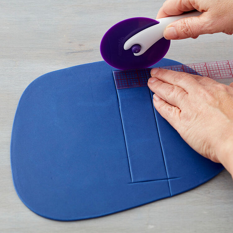 Cut strips of fondant equal in size using the Fondant Trimmer or a pizza cutter.