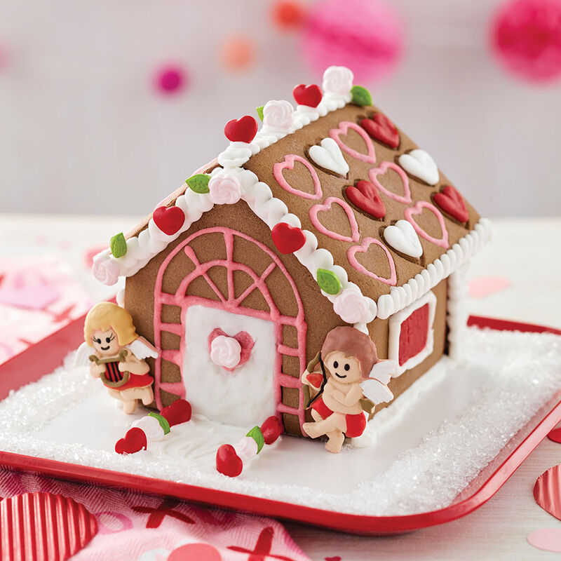 Valentine's Day chocolate cookie house, decorated with red, white, and pink hearts on the roof and cute male and female cupids on either side of the white door with pink heart window image number 1