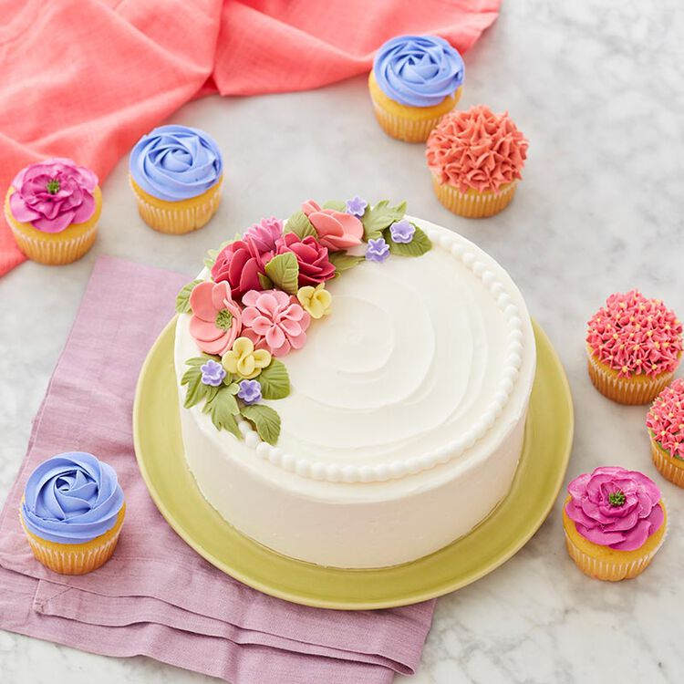 Round, white cake with different types of fondant flowers topping it.