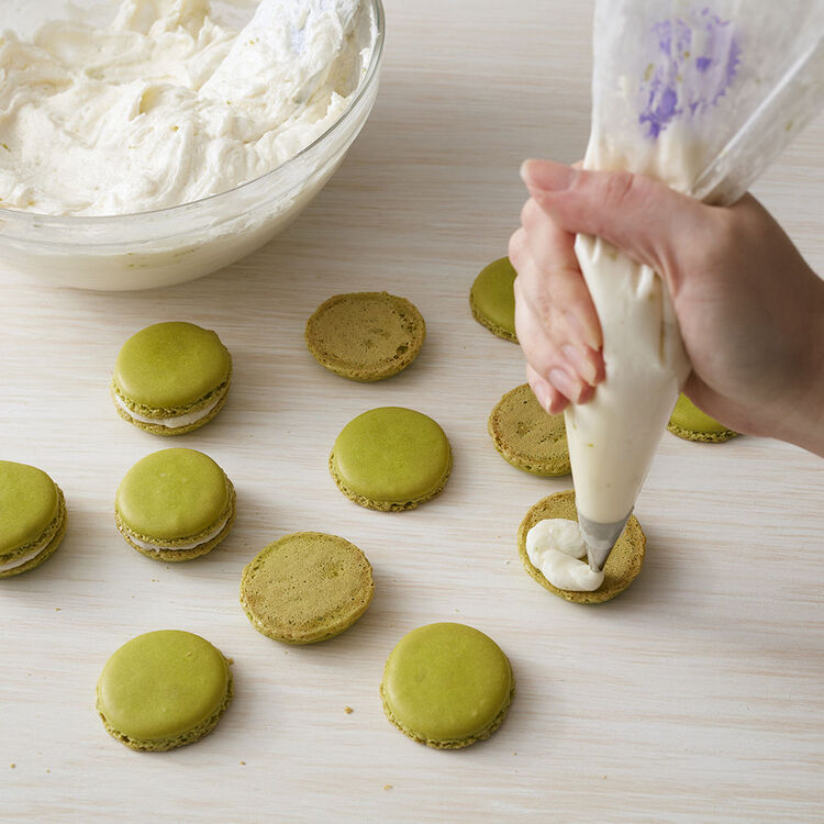 filling green macrons with key lime buttercream