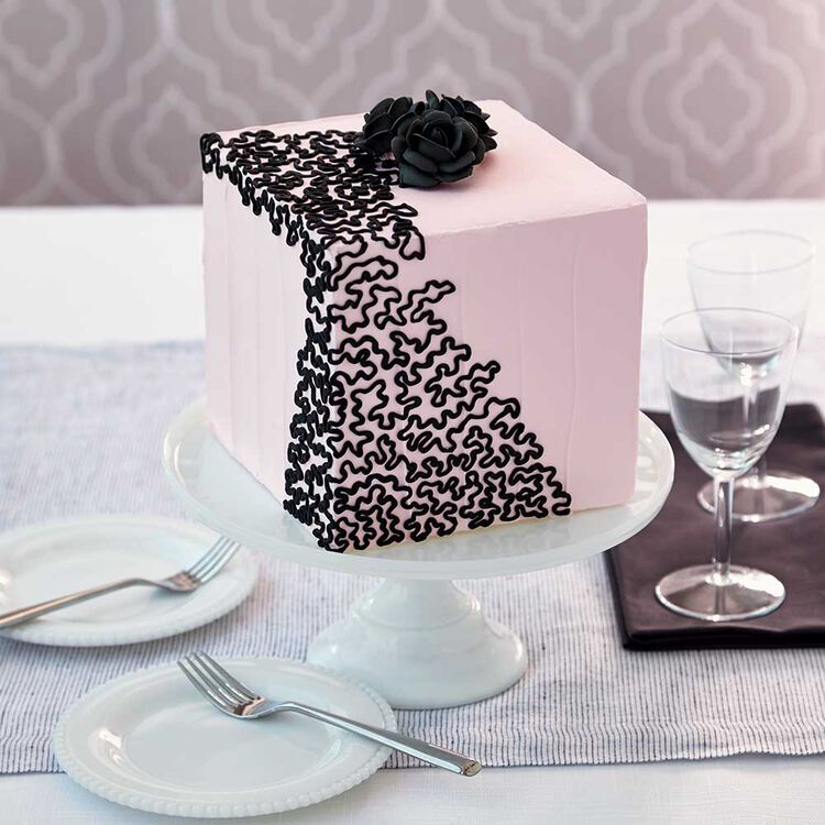 Pink square cake with black piped cornelli lace