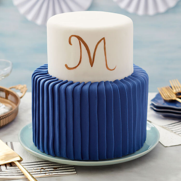"Two-tier cake, bottom tier with blue fondant pleats and top tier covered in fondant with ""M"" painted on its side."