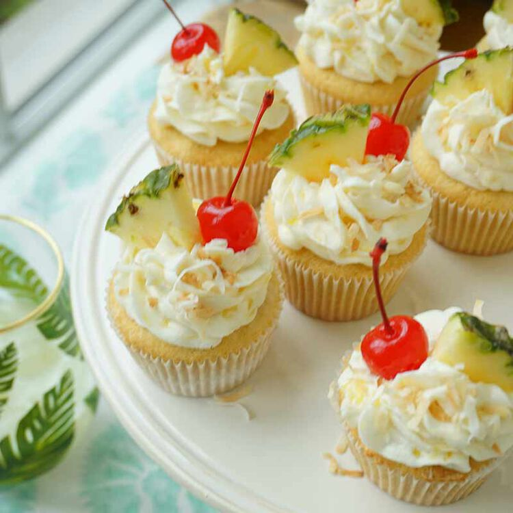 multiple pina colada cupcakes topped with pineapple flavored icing, coconut shreds, cherry and pineapple slice