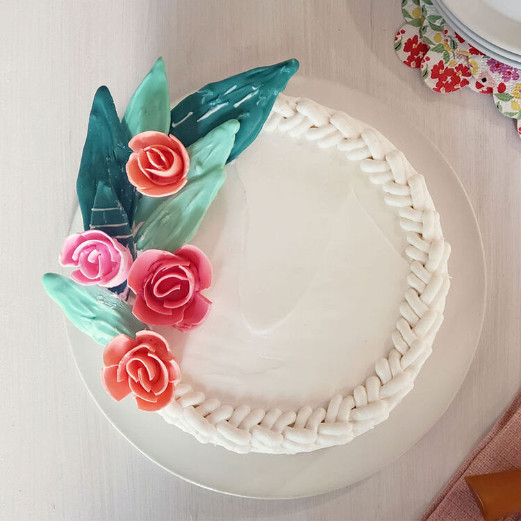 White buttercream cake with candy roses and leaves made using Candy Melts. Braided border around the top