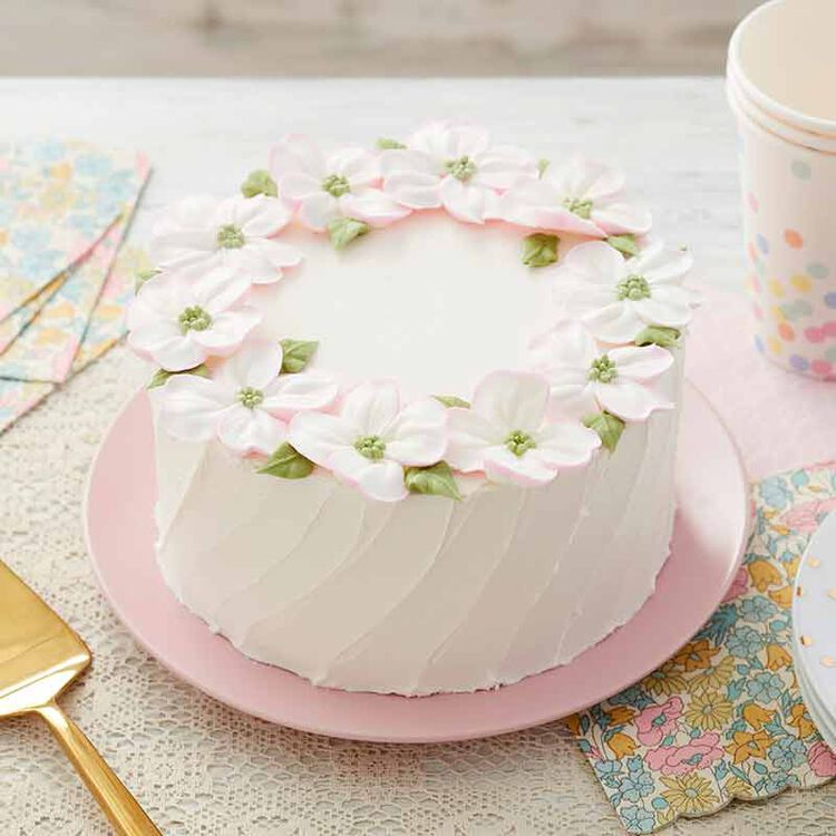 white buttercream frosted cake decorated with dogwood blossom flowers