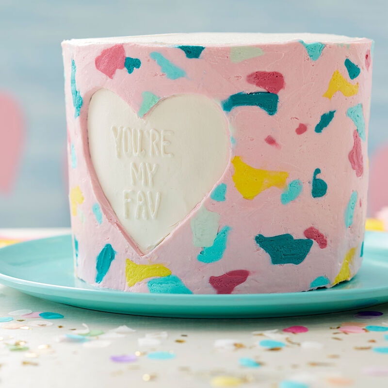 "Round Valentine cake decorated with buttercream with terrazzo pattern around the cake and a heart cut out. Inside the heart is ""You're My Fav"" in white. image number 0"