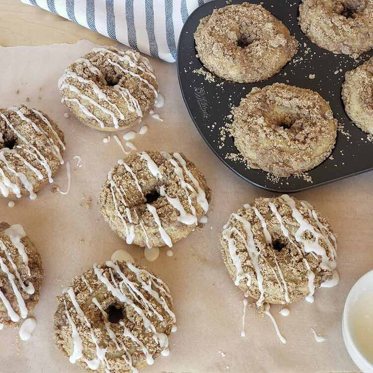 coffee cake-donuts with glaze sitting on parchment paper