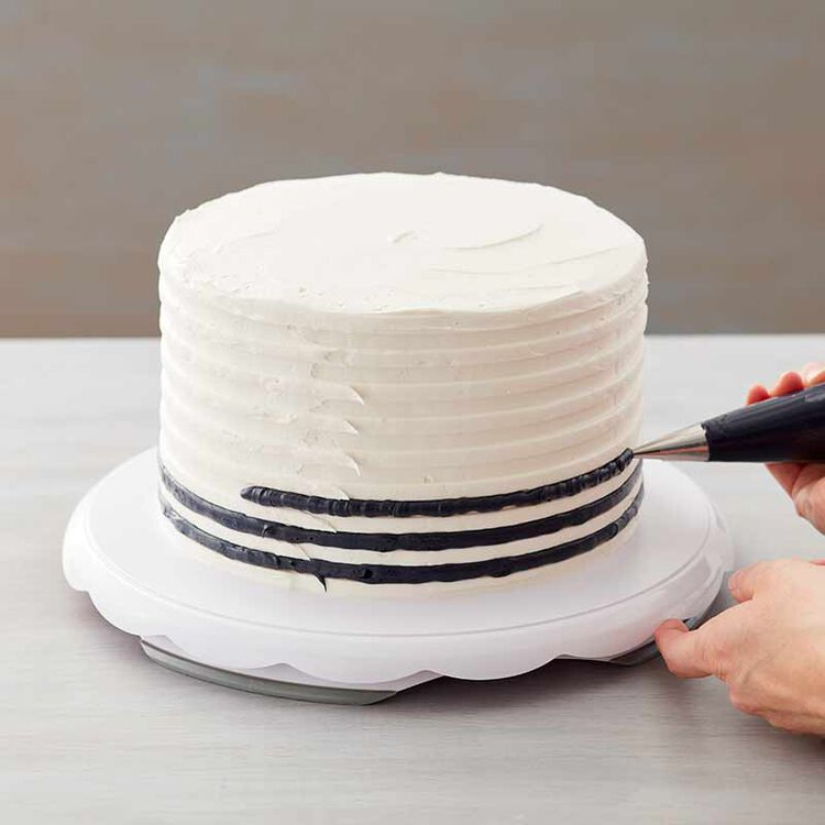 buttercream frosted cake being decorated with black stripes