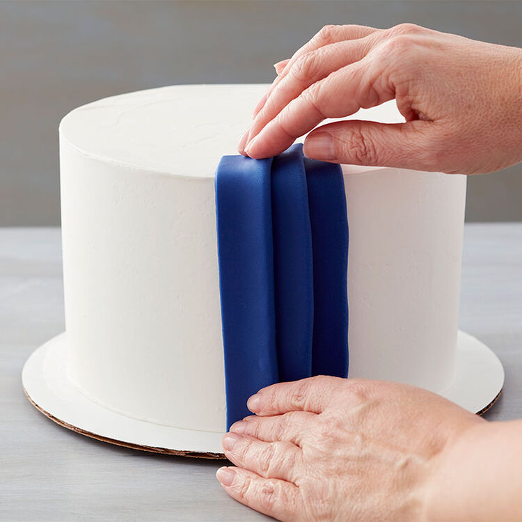 Folded fondant on a cake to look like pleats. For the last strip, fold over each long cut edge to the center, then place over the last pleat.