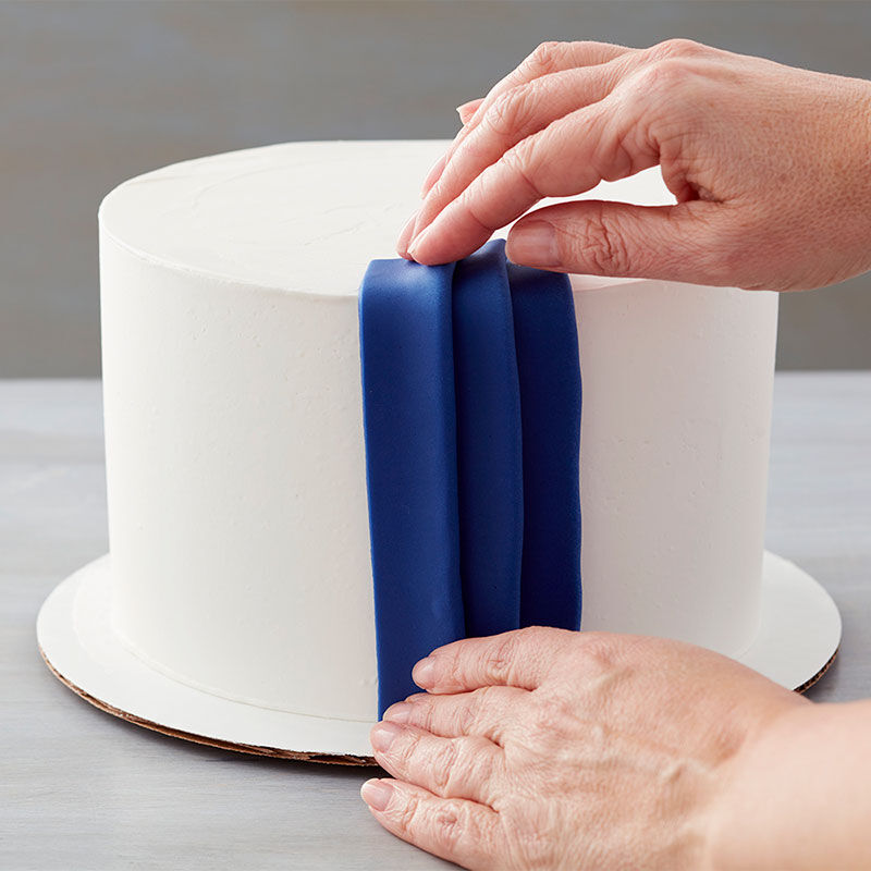 Folded fondant on a cake to look like pleats. For the last strip, fold over each long cut edge to the center, then place over the last pleat.  image number 0