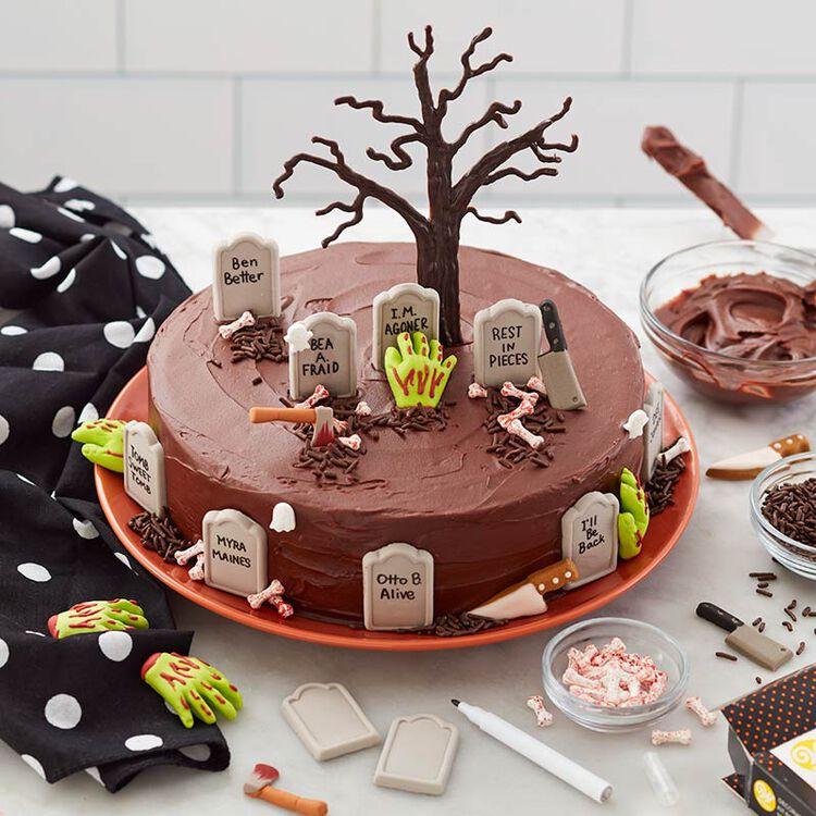 Halloween round cake with graveyard tombs, zombie hands and a haunted tree topping the cake.