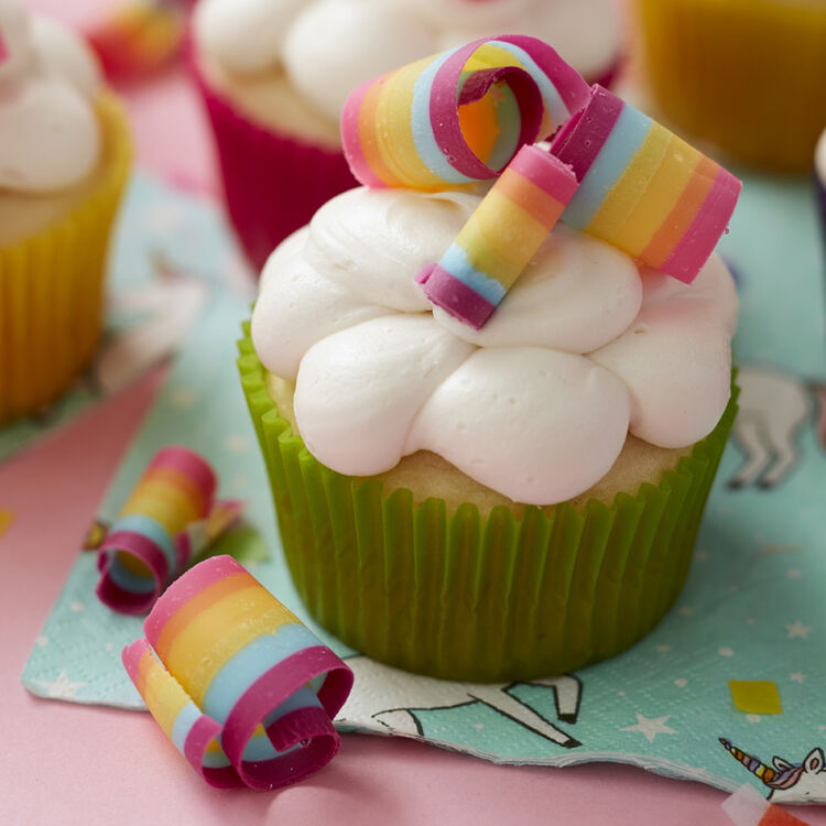 Rainbow candy curls made with Candy Melts, topping cupcakes with white buttercream frosting to look like a rainbow atop clouds