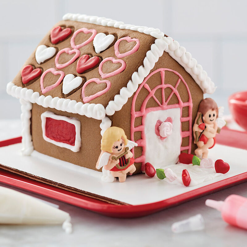 Valentine's Day chocolate cookie house, decorated with red, white, and pink hearts on the roof and cute male and female cupids on either side of the white door with pink heart window image number 0