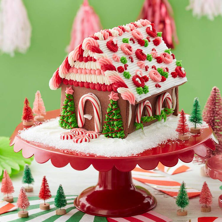 Pink, red, and white chocolate gingerbread house with two trees on either side of the front door