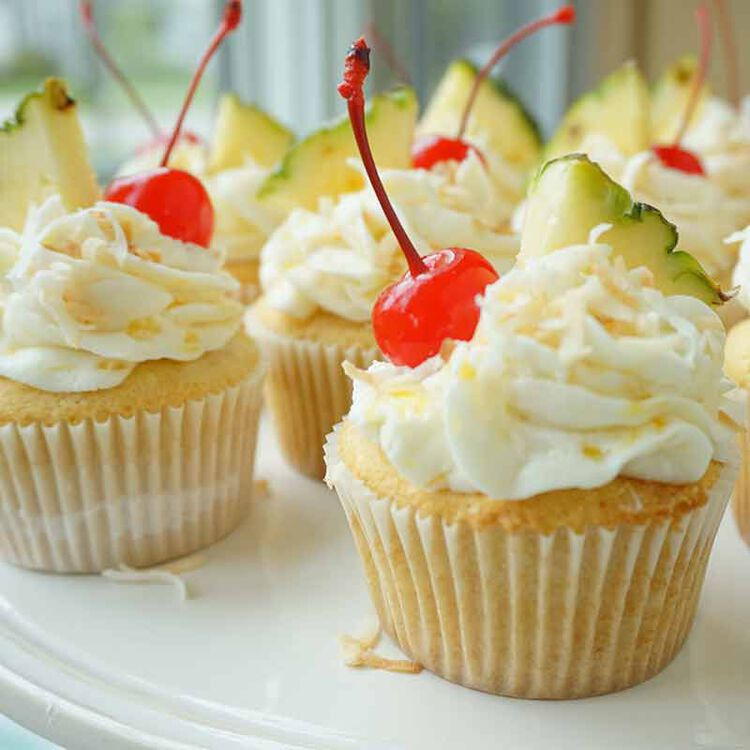 pina colada cupcake topped with pineapple flavored icing, coconut shreds, cherry and pineapple slice on a plate