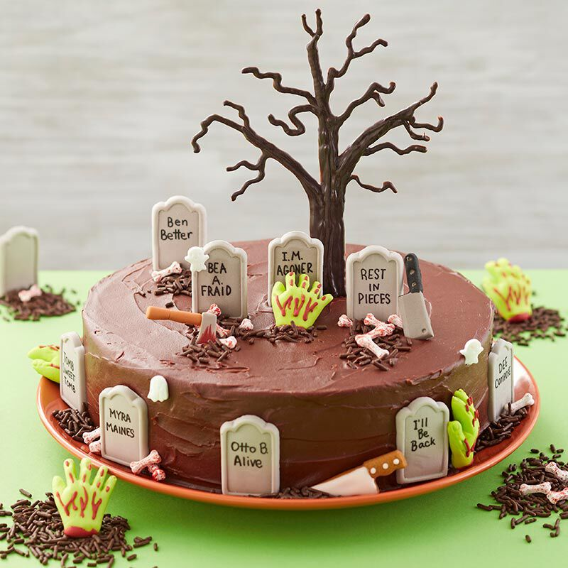 Halloween round cake with graveyard tombs, zombie hands and a haunted tree topping the cake. image number 0