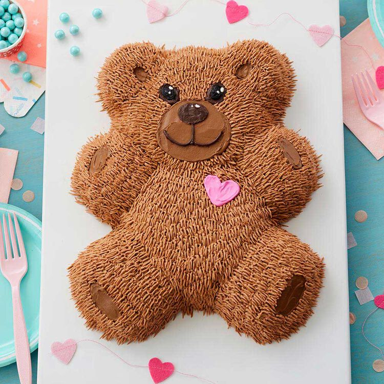 Teddy bear shaped cake with pink heart and brown buttercream piped to look like fur