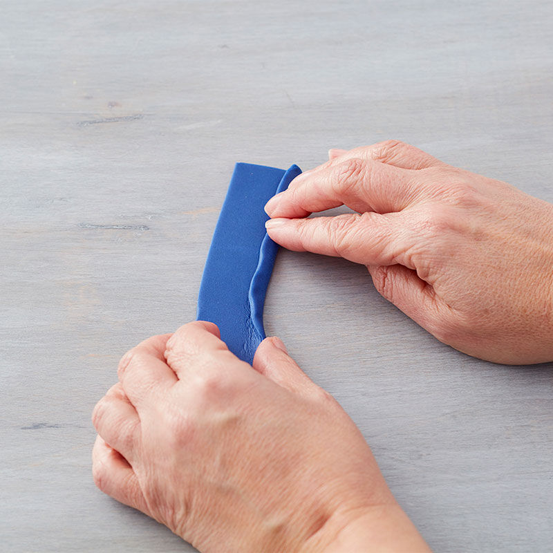 Fold down ¼ in. along the long length of the strip. Attach to the cake with the fold side down using piping gel. image number 3