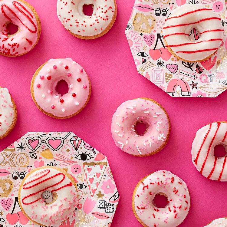 Doughnuts with pink and white icing and topped with a variety of pink, red, and white sprinkles laid out on a bright pink tablecloth